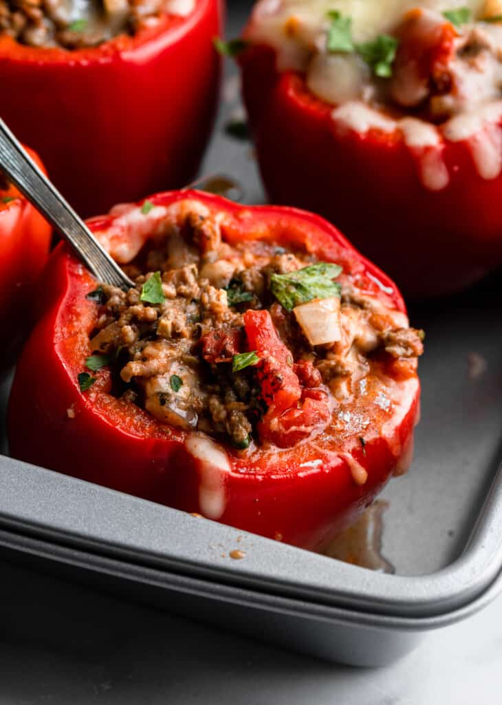 a Keto Stuffed Peppers in a baking dish with a fork inserted