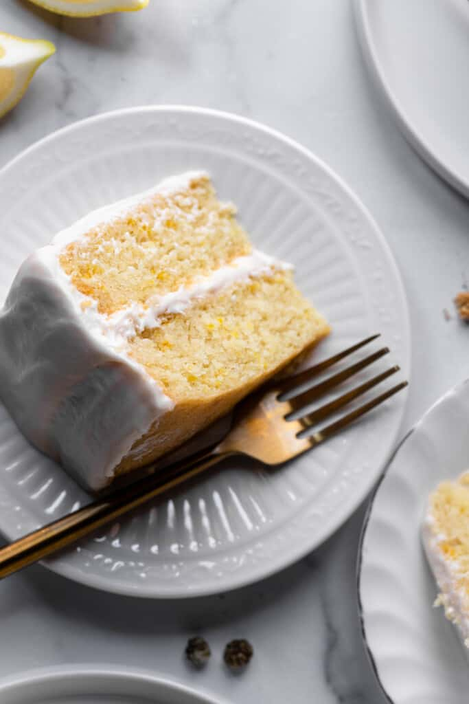 one slice of Vegan Lemon Cake on a small plate with a fork