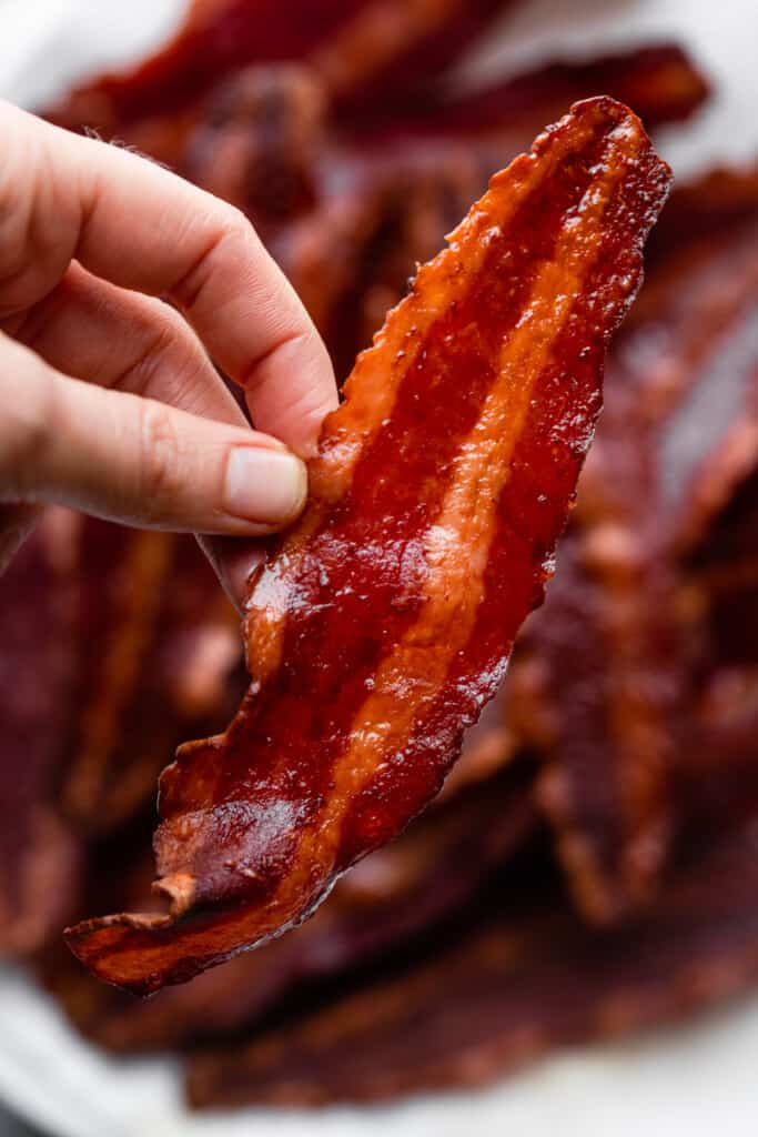 one slice of Air Fryer Turkey Bacon being held up by hand