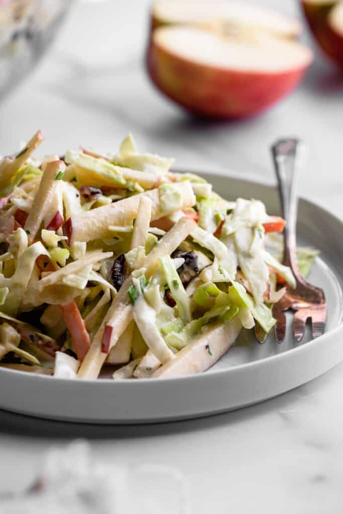 a plate full of Apple Coleslaw with a fork