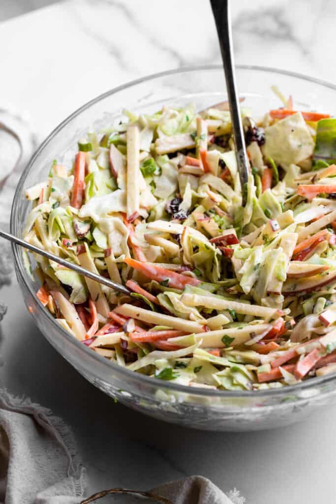 a large serving bowl full of Apple Coleslaw