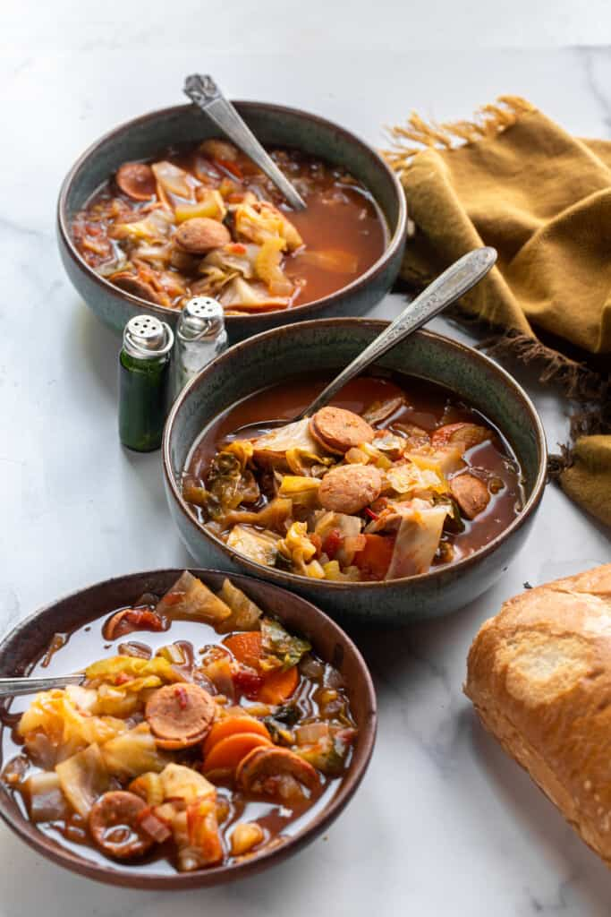 bowls of Cabbage Soup with Sausage with spoons