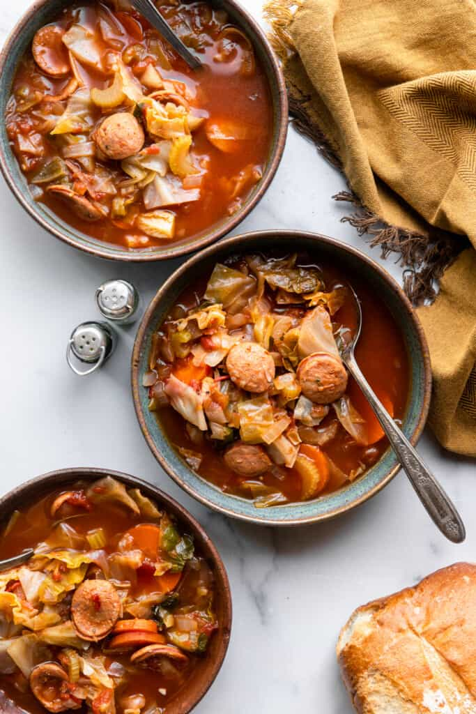 several bowls of Cabbage Soup with Sausage on a table