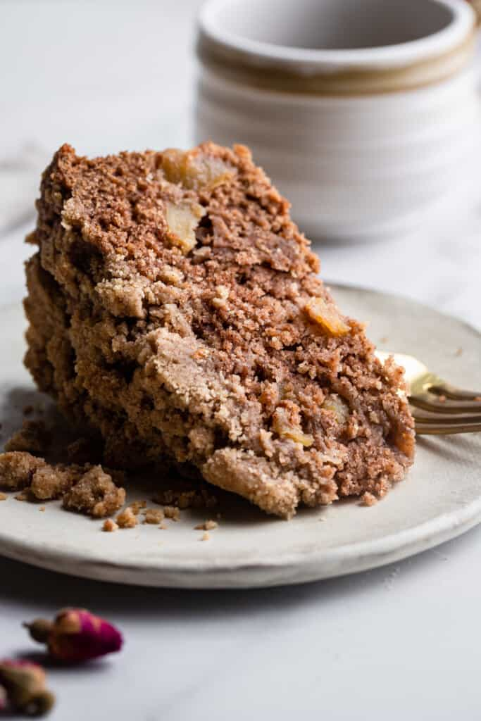 a slice of Vegan Apple Cake on a small plate with a fork