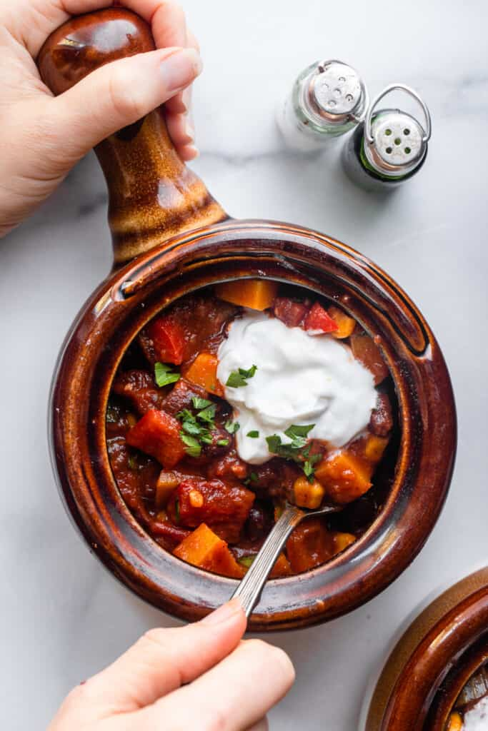 a soup cup full of Butternut Squash Chili with a spoon
