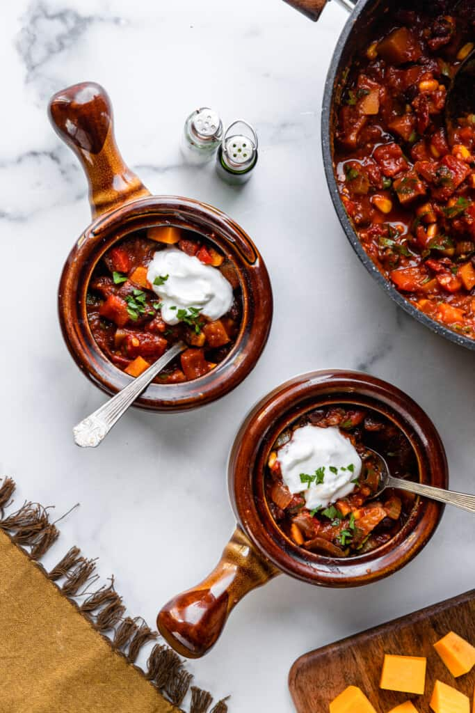 two soup cups filled with Butternut Squash Chili and sour cream