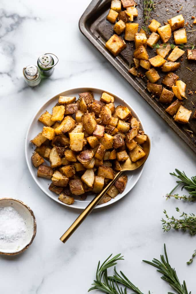 a bowl and baking sheet of Roasted Russet Potatoes