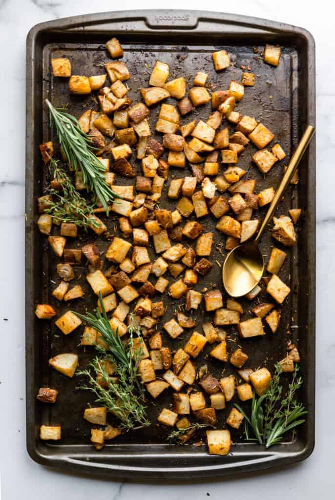 Roasted Russet Potatoes on a backing sheet with a spoon and rosemary