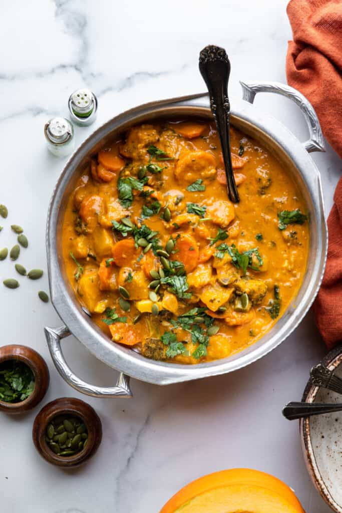 a large pot full of Thai Pumpkin Curry with a spoon