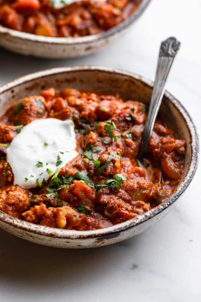a bowl of Turkey Pumpkin Chili with sour cream on top