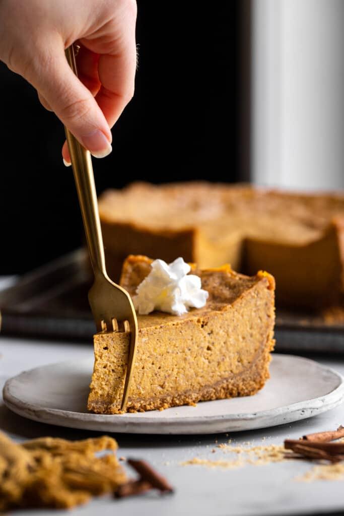 a fork cutting into Vegan Pumpkin Cheesecake