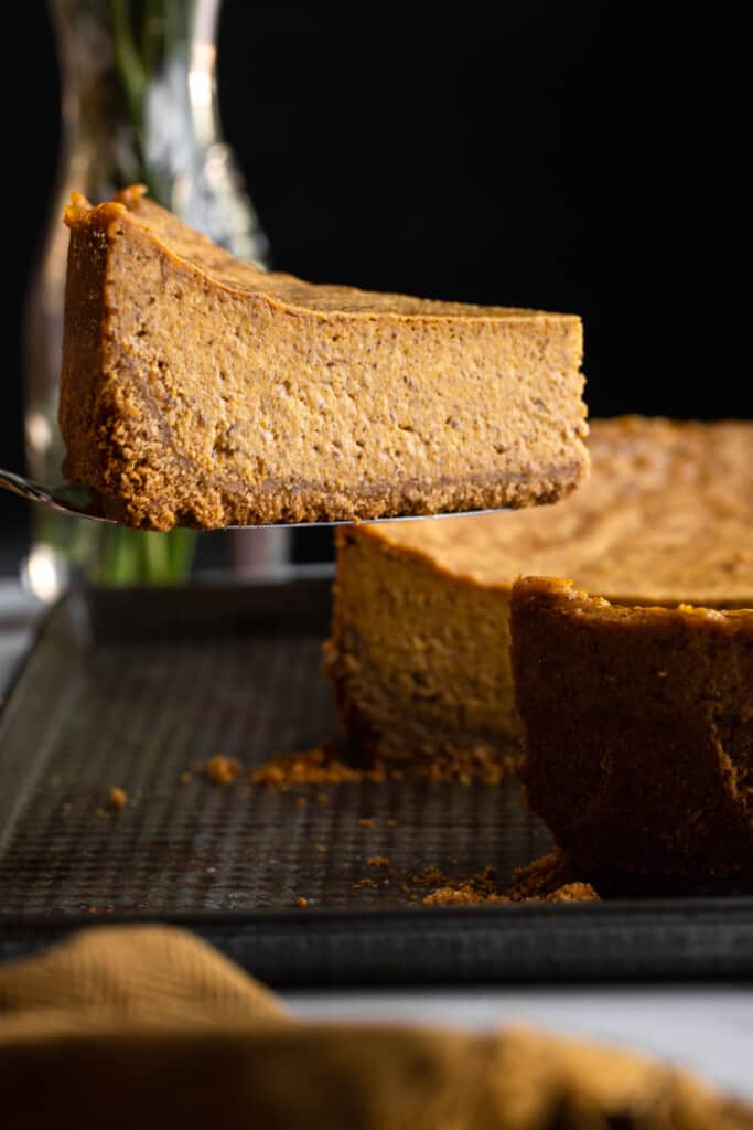 a slice of Vegan Pumpkin Cheesecake being lifted out of the cake
