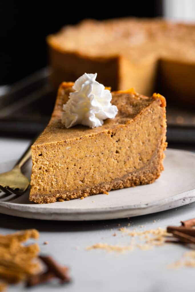 a slice of Vegan Pumpkin Cheesecake on a small plate with whipped cream